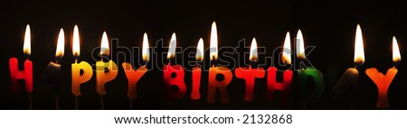 Panoramic Happy Birthday candles alight against a dark background
