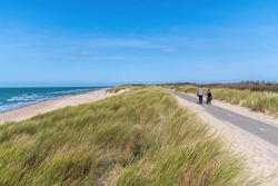 Panoramic high level view over the dunes and sandy beach of the city of Vlissingen in the Netherlands with a couple on a bicycle passing by on the bike path