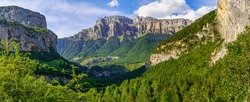 Panoramic high rocky mountain landscape with green forests. Ordesa Pirineos National Park.