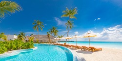Panoramic holiday landscape. Luxurious beach resort hotel swimming pool and beach chairs or loungers under umbrellas with palm trees, blue sunny sky. Summer island seaside, travel vacation background