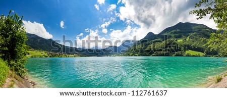 Panoramic image from the shore of a Green and Blue Mountain lake in the Swiss Alps