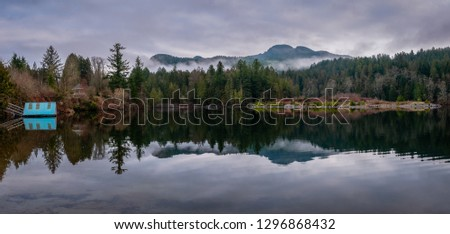 Panoramic image of a misty morning lakeshore with a small boathouse and a gazebo with a backdrop of mountains and cloudy sky. #1296868432