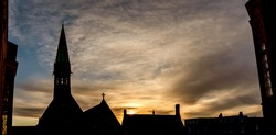 Panoramic image of a sunrise over the Harrow School with silhouette of Harrow School Chapel and Vaughan Library, England