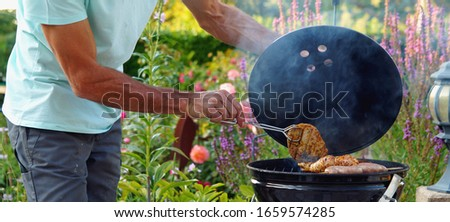panoramic image of Barbecue grill. the man hand is grilling with pair of tongs , hand of a man in work trousers turning delicious grilled meat over the coals on a bbq grill. BBQ Background Theme