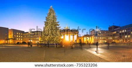 Panoramic image of Brandenburger Gate in Berlin with Christmas tree on a sunset with evening illumination.