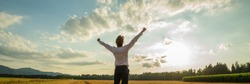 Panoramic image of successful businessman standing under majestic sky with his arms raised up high in triumph.