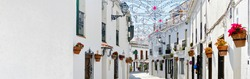 Panoramic image white copy space view, empty street famous village of Mijas in Spain. Charming narrow streets with New Year decorations, hanging flower pots on walls, no people. Costa del Sol, Málaga