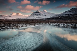 Panoramic landscape, highland of Iceland, dramatic sky, majestic mountains, frozen lake and snow covered tops, pink coloured clouds