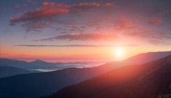 Panoramic landscape of colorful sunrise in the mountains. View on foggy hills covered by forest. Concept of the awakening wildlife.
