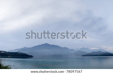 Panoramic landscape of lake with mountain under cloudy sky, famous attraction, Sun Moon Lake situated in Yuchi, Nantou, Taiwan, Asia.
