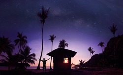 Panoramic landscape of man standing on the coconut beach with a million stars and sunrise early morning.