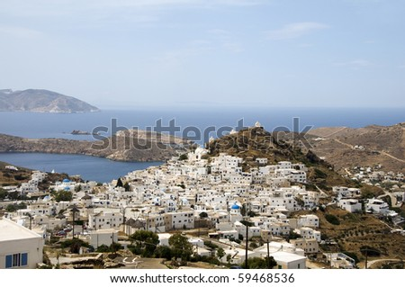 panoramic landscape of typical Greek island architecture white washed Cyclades buildings churches with view of Mediterranean sea harbor Ios island Greece