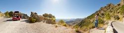 Panoramic landscape photo of Sierra de Grazalema national park. Female tourist enjoys amazing view of the landscape. Stopped car. Beautiful scenery. Blue sky. Malaga. Andalusia. Spain.