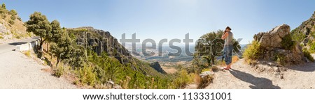 Panoramic landscape photo of Sierra de Grazalema national park. Female tourist taking pictures of the amazing landscape. Beautiful scenery. Blue sky. Malaga. Andalusia. Spain.
