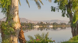 Panoramic landscape view across nile river to luxor west bank with mountains and reflection in water