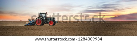 Panoramic landscape view of the tractor on the field sowing. Planting seeds mechanization.