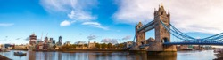 Panoramic London skyline with iconic symbol, the Tower Bridge and Her Majesty's Royal Palace and Fortress, known as the Tower of London as viewed from South Bank of the River Thames in the morning