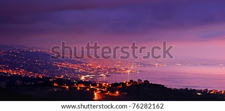 Panoramic mountains city at night with purple sky & sea