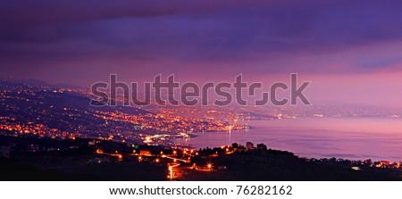 Panoramic mountains city at night with purple sky & sea