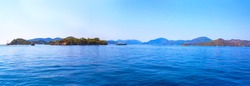 Panoramic nautical seascape. Calm sea, boat, green islands and pale blue mountains on the horizon, clear sky. Background. Mediterranean, Turkey