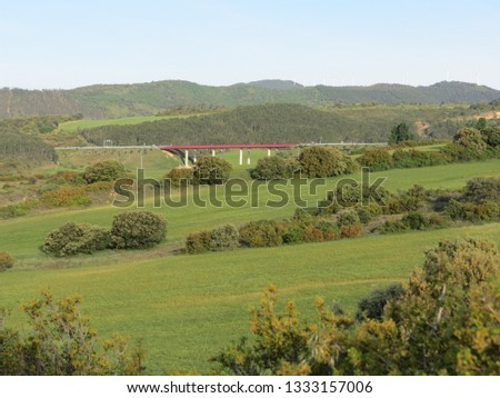 Panoramic Navarra (Spain) landscape with green meadows and modern red bridge in the distance #1333157006
