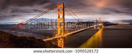 Panoramic night view of Golden Gate Bridge, San Francisco downtown area in the background, California