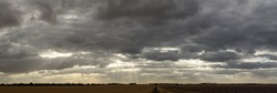 panoramic of a dramatic cloud filled late afternoon sky stretching over large farm fields in rural Victoria just after harvest with a dirt road down the middle.