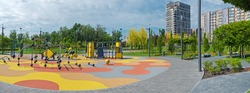 Panoramic of colorful large playground in city park. Empty modern outdoor playground in springtime. Beautiful urban place for kids games and sport