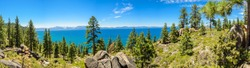 Panoramic of Lake Tahoe during a sunny day with trees in close-ups and turquoise lake in downtown, Nevada and California, US