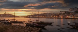 Panoramic of Porto cityscape in sunset with river on the front and wine carrier ship in  foreground and city of Porto in background, Portugal.