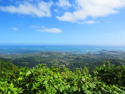 Panoramic of the Caribbean coast of the French Antilles. Exotic landscape of tropical vegetation, Caribbean sea and blue sky with white clouds. Nature and landscape background.