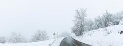 Panoramic of the snowy road going up to Alto de la Cobertoria towards Proaza, Asturias, Spain