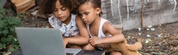 panoramic orientation of poor african american kids using laptop outside
