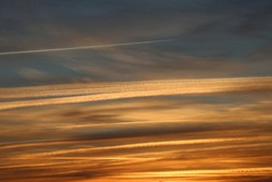 Panoramic outdoor view of a blue orange sky with many aeroplanes traces. White lines and bands drawn in all directions in the cloudy sky. Condensation in the air. Abstract colorful view in the nature.