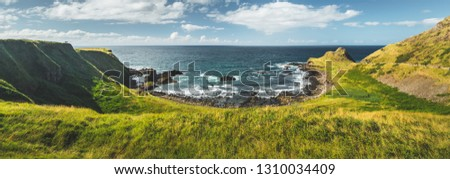 Panoramic overview of the Northern Ireland shoreline. Amazing Irish landscape. Green grass covered shore surrounded by the ocean water. Cozy bay under the cloudy sky background. Wilderness. #1310034409