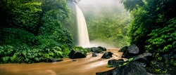 Panoramic photo Deep forest wild waterfall at tropical island on background mountain and green jungle tree nature