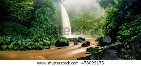 Panoramic photo Deep forest wild waterfall at tropical island on background mountain and green jungle tree nature stock photo