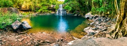 Panoramic photo landscape / Waterfall hidden in the tropical jungle surrounded by a natural swimming pool with clear fresh water on background green forest tree and mountain / Asia