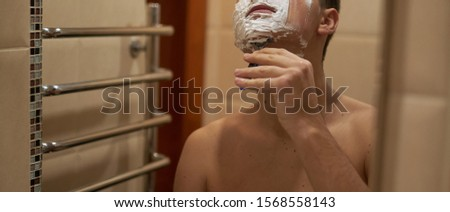 Panoramic photo of a shaving guy. The guy is shaving. Soft focus.