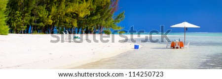 Panoramic photo of a tropical beach with picnic table set in a shallow water