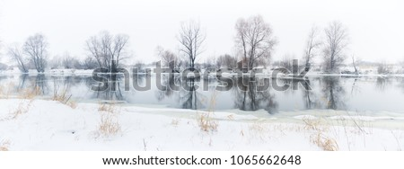 panoramic photo of a winter river with snowy banks and ice. #1065662648