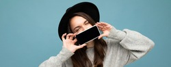 panoramic Photo of Beautiful positive woman person wearing black hat and grey sweater holding mobilephone showing smartphone isolated on background with fantastic eyes