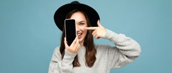 panoramic Photo of Beautiful positive woman wearing black hat and grey sweater holding mobilephone showing smartphone isolated on background looking at camera