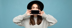 panoramic Photo of Beautiful positive young female person wearing black hat and grey sweater holding mobilephone showing smartphone isolated on background looking at camera