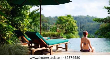 Panoramic photo of beautiful woman relaxing at swimming pool