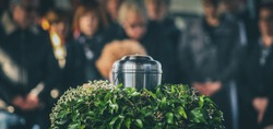 Panoramic photo of metal urn with ashes of dead person on funeral, with people mourning in background on memorial service. Sad grieving moment at end of life. Last farewell to a person in urn.