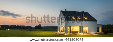 Panoramic photo of modern house with outdoor and indoor lighting, at night #441508093