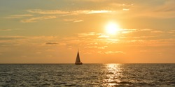 Panoramic photo of sailing boat sails on the sea at sunset. Copy space for text.