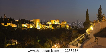 Panoramic photo of the Alhambra at night. Hill with trees. Sunset. Granada. Andalusia. Spain.
