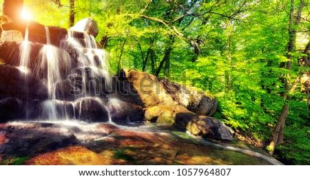 Panoramic  photo of the waterfall. Flowing streams of water on the rocks among the bright green trees. Spring bright day. Uman. Sofievsky Park. Ukraine.
